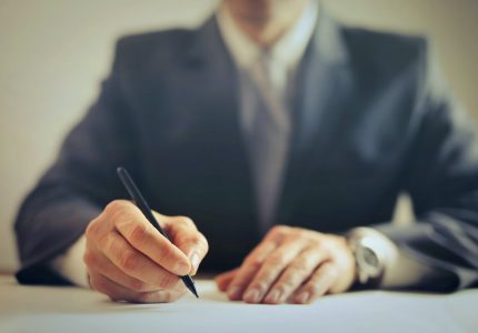 crop businessman signing contract in office